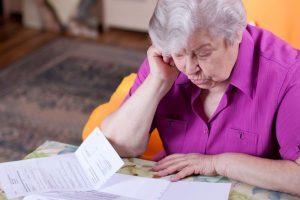 Frau liest die Begründung der Ablehnung der Ablehnung einer Pflegestufe.